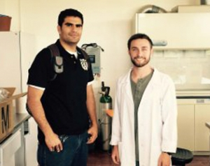 Here Alex (right) is shown in his lab coat with graduate student and lab mentor Oscar (left).